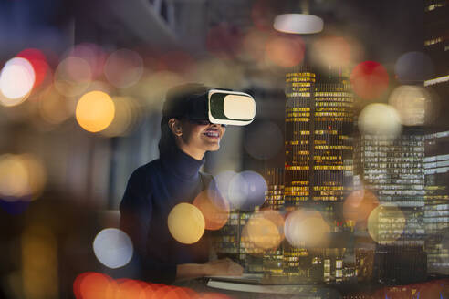Businesswoman with virtual reality glasses in highrise office at night - CAIF28195