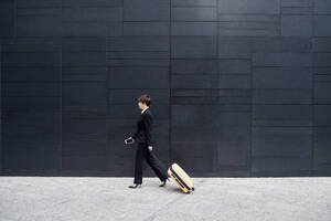 Businesswoman with suitcase walking on sidewalk by modern building in city - MEUF01273