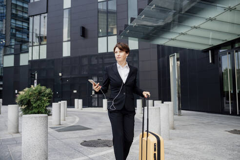 Female professional listening music while walking with suitcase against modern building - MEUF01294