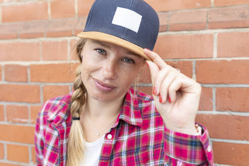 Close-up of woman with braided hair wearing cap against brick wall - WPEF03207