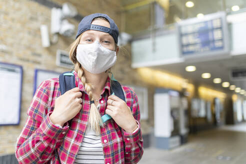 Close-up of woman with braided hair wearing mask and cap while standing at tube station - WPEF03210