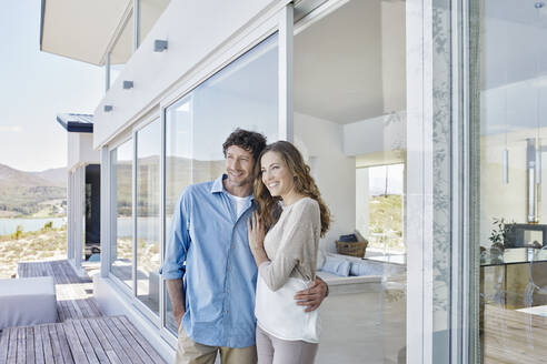 Happy couple standing at luxury beach house - RORF02259