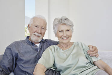 Portrait of smiling senior couple sitting on a couch in a villa - RORF02271