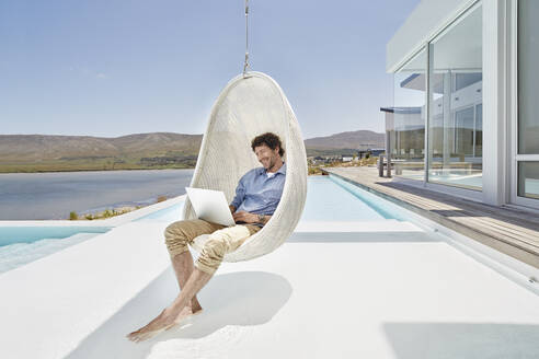 Man sitting in hanging chair above swimming pool using laptop - RORF02277