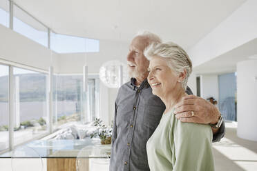 Happy senior couple in luxury beach house looking out of window - RORF02292