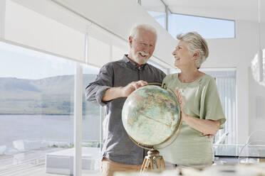 Happy senior couple with globe in a luxury villa - RORF02298
