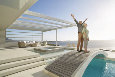 Carefree senior couple standing on bridge above a swimming pool at a luxury beach house - RORF02310
