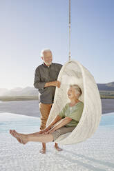 Happy senior couple with woman sitting in hanging chair above swimming pool - RORF02322