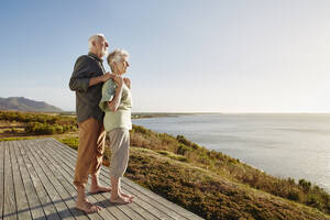 Senior couple enjoxing the view on wooden terrace at the sea - RORF02328