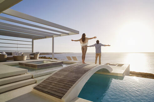 Couple standing on bridge above a swimming pool enjoying the view - RORF02331