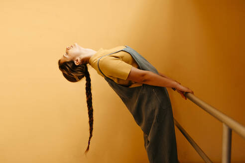 Young woman bending backwards in front of orange wall - TCEF00901