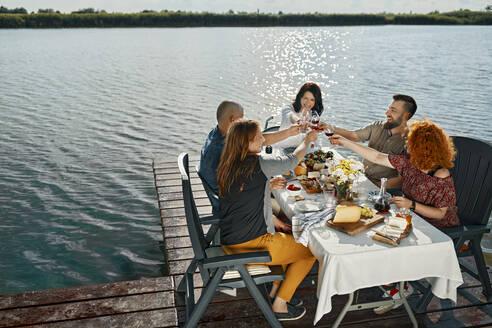 Friends having dinner at a lake clinking wine glasses - ZEDF03526