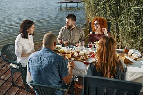 Friends having dinner at the lakeside - ZEDF03529