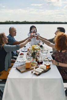 Friends having dinner at a lake clinking wine glasses - ZEDF03535