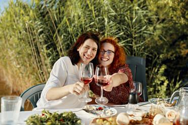 Portrait of two happy female friends having dinner at the lakeside raising wine glasses - ZEDF03574