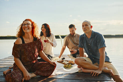 Happy friends having picnic on jetty at a lake at sunset - ZEDF03580