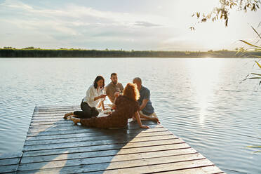 Friends having picnic on jetty at a lake at sunset - ZEDF03583