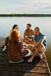 Friends having picnic on jetty at a lake - ZEDF03589