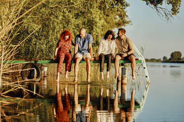 Friends reflected in water sitting on jetty at a lake - ZEDF03592