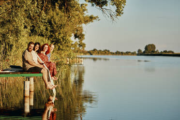 Portrait of smiling friends reflected in water sitting on jetty at a lake - ZEDF03598