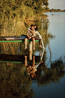 Affectionate couple reflected in water sitting on jetty at a lake - ZEDF03601