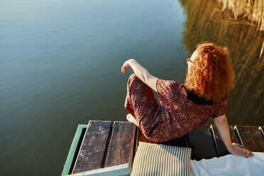 Redheaded young woman sitting on jetty at a lake at sunset - ZEDF03607