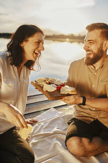 Happy couple having picnic on jetty at a lake at sunset eating cheese - ZEDF03616