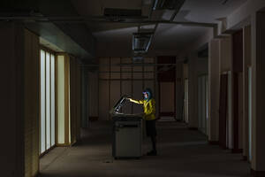 Businesswoman with dyed hair operating photocopier standing in old abandoned office - JMPF00127