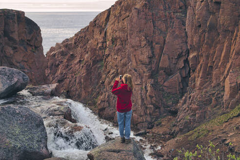 Young woman photographing waterfall while standing on rocky mountain at Teriberka, Murmansk Oblast, Russia - KNTF04902