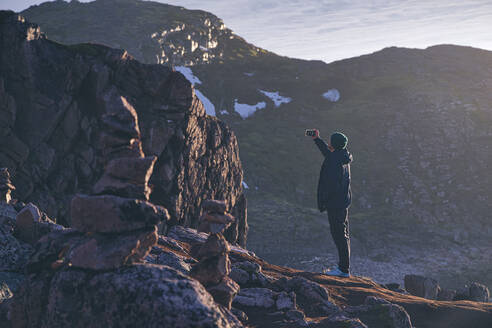 Young man taking selfie while standing on rocky mountain at Teriberka, Murmansk Oblast, Russia - KNTF04908