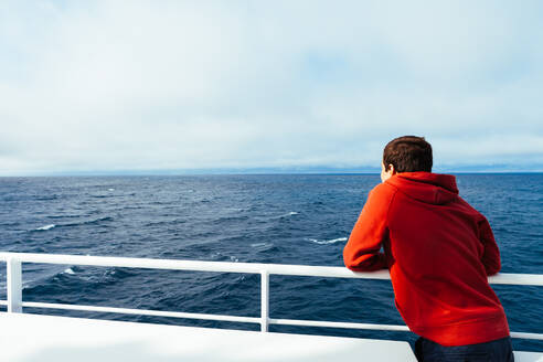 Back view of child in red hoodie standing on ship deck looking at endless blue sea expanses - ADSF00115