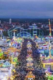 Germany, Bavaria, Munich, Drone view of crowds of people celebratingOktoberfest in vast amusement park at dusk - MMAF01351