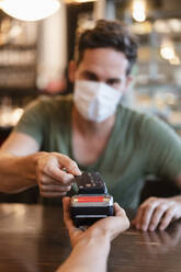 Man with protective mask paying with credit card in restaurant - DIGF12748