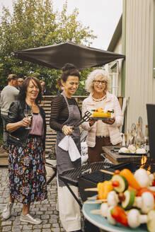 Happy elderly female friends preparing dinner on barbecue at back yard - MASF18977