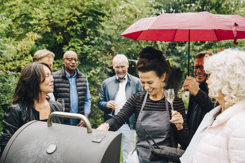 Smiling female friends cooking dinner on barbecue grill during party while it rains - MASF19007