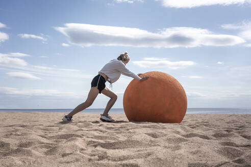 Young woman rolling orange stone at beach - VPIF02583