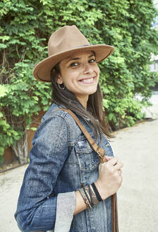 Happy woman wearing sun hat and denim jacket while standing on footpath during sunny day - VEGF02475
