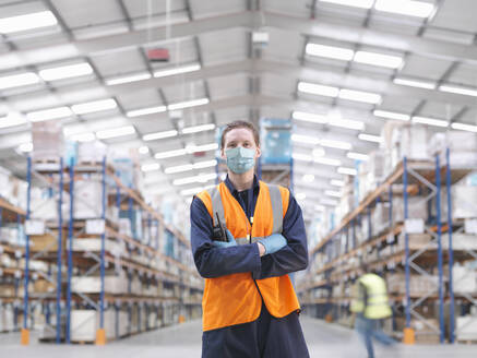 Man wearing surgical face mask and high visibility vest working in a large warehouse. - CUF55692