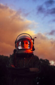 Girl wearing old space helmet at sunset - ADSF00381