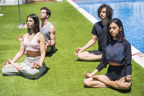 Young multi-ethnic friends meditating while practicing yoga on grass at back yard during sunny - JSMF01620