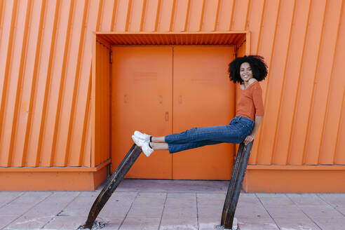 Smiling young afro woman sitting on damaged metal against orange door - TCEF00915
