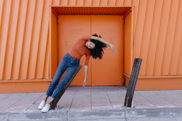 Young woman leaning on damaged metal with arm raised against orange door - TCEF00918