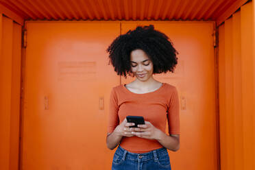 Smiling young woman using smart phone while standing against orange door - TCEF00924
