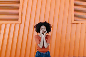 Young afro woman with eyes closed standing against orange metal wall - TCEF00927