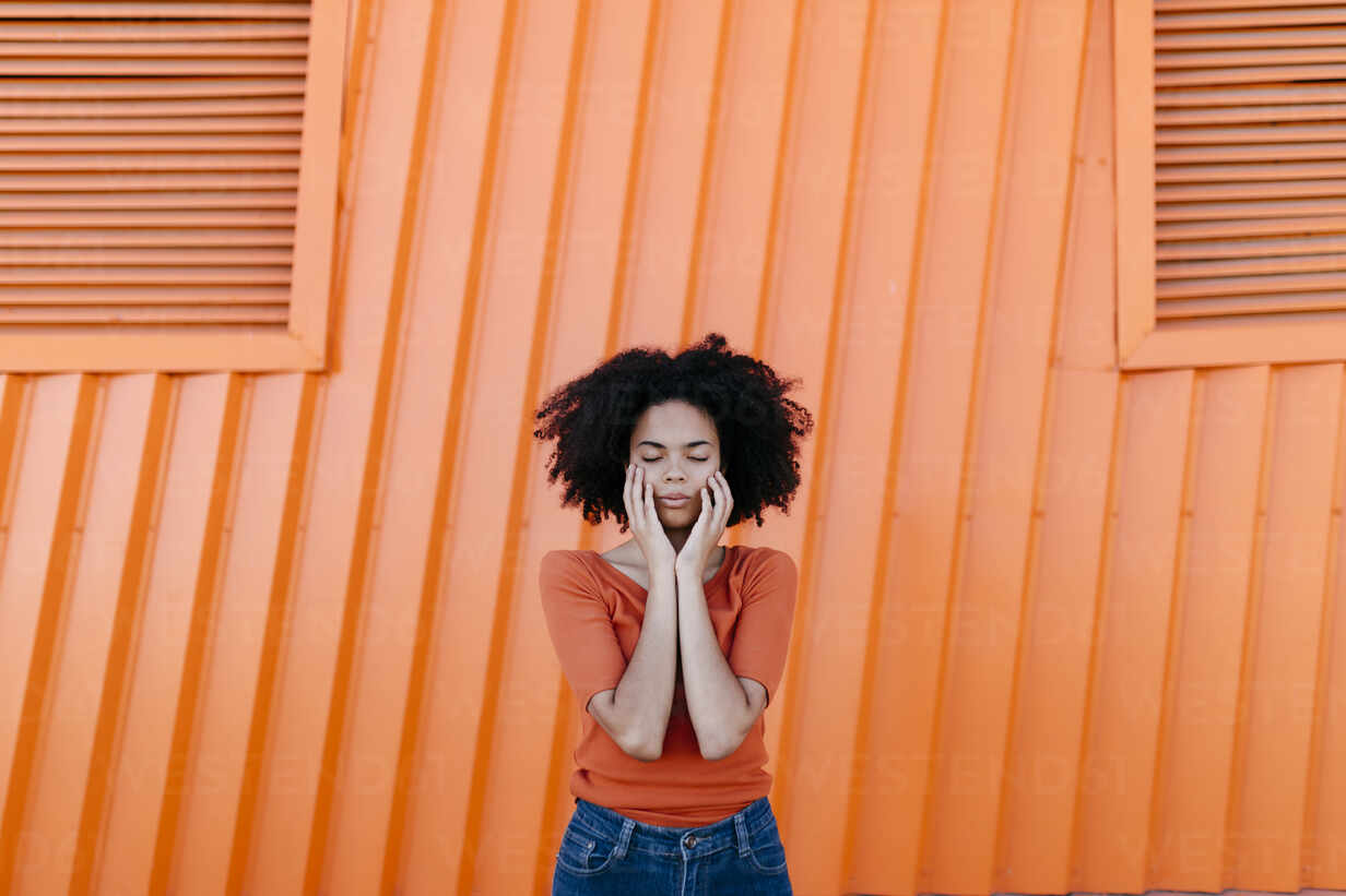 Young afro woman with eyes closed standing against orange metal wall - TCEF00927 - Tania Cervián/Westend61