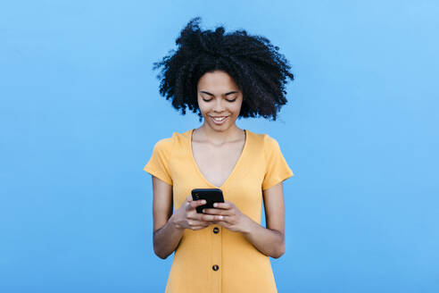 Smiling young woman using smart phone while standing against blue wall - TCEF00930