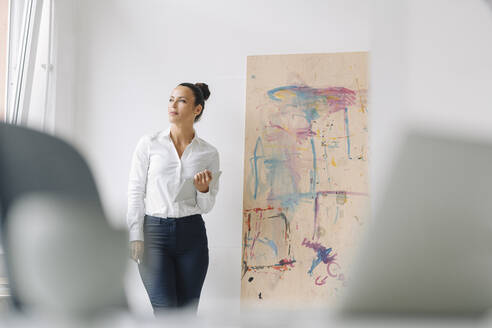 Thoughtful businesswoman holding digital tablet while standing against wall in home office - JOSEF01281
