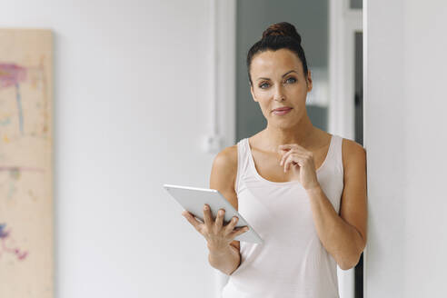 Smiling mid adult woman holding digital tablet while standing by wall at home office - JOSEF01323