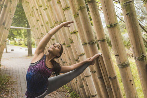 Flexible young woman stretching while leaning on bamboo at park - DSIF00013