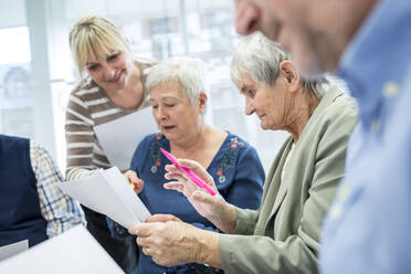 Seniors in therapy group in retirement home writing down notes on sheets of paper - WESTF24606